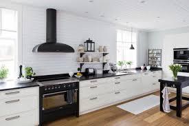black appliances black hood built in cabinet white cabinet tiled wall wooden floor black table floating