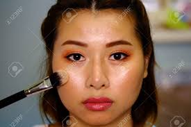 stock photo woman thailand holding a makeup powder brush to her acne face no effect selective focus