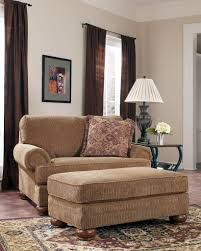 brown comfortable chair and ottoman added with black wooden lamp table placed on brown flm pattern carpet with super comfy reading chair and comfy