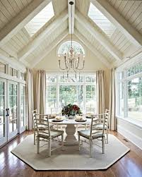 you are surrounded by light in this dining room by carolina design ociates i love the painted wood vaulted ceiling with skylights and the french doors