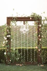 picture of a gorgeous backdrop with a large vintage wooden frame decorated with crystals and a crystal chandelier greenery and blush blooms