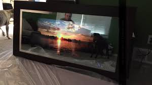 the whole frame was created on a french cleat system the other half of the cleat is mounted on the wall when the mirror television hangs and the cords