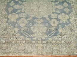 a evenly distressed antique persian tabriz rug with classic medallion and border