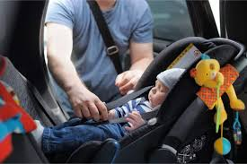 dad putting baby in the car seat