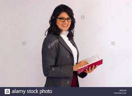 Smiling woman in <b>business suit</b> with <b>notebook</b> and <b>pen</b> looking at ...