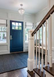 Lovely entry features blue beadboard door flanked by windows dressed ...