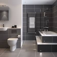 large dark grey tiles surrounded by white grout and white appliances makes this bathroom look clean sleek and relaxing