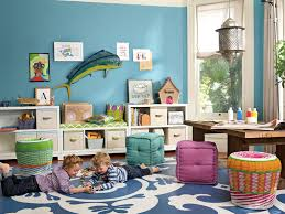 funny small kids playroom ideas with blue patterned area rug and cubical ottomans plus wooden table also blue painted wall and white open shelves