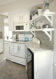 stunning white and gray kitchen with white kitchen cabinets and kashmir white granite countertops with lowe s emser tile s lucente in morning fog tile