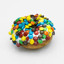 image of a plain cake doughnut with vanilla frosting and covered with mini m ms