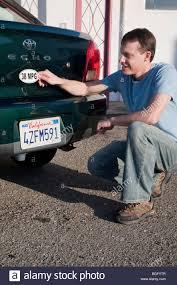 Mid adult man placing a 38 miles per gallon fuel efficiency bumper ...
