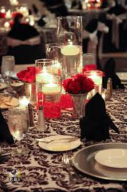 Classic red rose centerpieces with floating candles in tall vases.