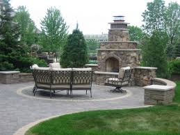 cascade style stone outdoor fireplace and wrought iron patio furniture set