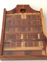 wooden perpetual wall calendar with wood tiles and wheel to turn months