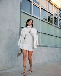 we see tailored white pea coat dd over high neck white ribbed knit mini dress the outfit is completed thanks to strappy lace up sandals