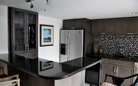 small kitchen design with black pearl granite countertops mosaic backsplash and brown wooden cabinet ideas