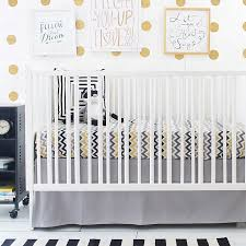 white baby crib in the nursery room with chevron beddinggray and