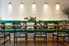 view in gallery lighting highlights the beauty of the painted brick wall in the dining room design