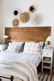 bedroom decorations in neutral colors with a reclaimed wood headboard and a collection of homemade african