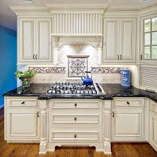 furniture beige tile backsplash and black granite countertops connected by white wooden kitchen cabinet