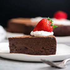 side view of a piece of flourless chocolate cake on a plate with whipped cream and