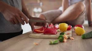 kitchen table with food. Closeup View Of African Guy\u0027s Hands Cutting Vegetables Preparing Food While His Caucasian Girlfriend Is Sitting Kitchen Table With E