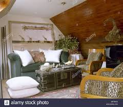 exotic living room furniture. Exotic Sitting Room With A Sloping, Wood-panelled Ceiling, Sofa, Coffee Table, And Animal Print Chairs. Living Furniture