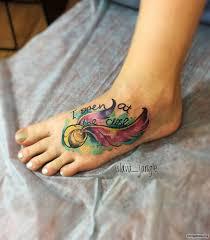 мяч с крыльями и надписью тату на ступне у девушки добавлено