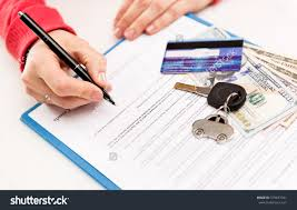 young female leasing consultant signing car stock photo  young female leasing consultant signing car insurance contract in the office closeup of vehicle