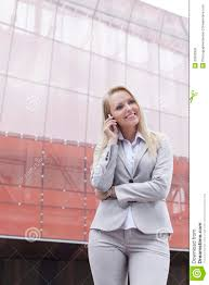 beautiful young businesswoman using mobile phone while standing against office building beautiful office building