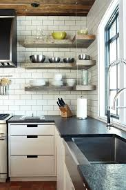 industrial wooden kitchen shelves supported by ceiling mounted wires white subway tiles backsplash black countertop flat