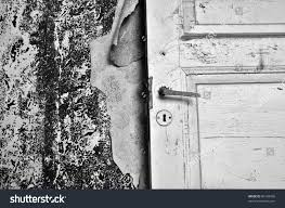 torn wallpaper and old door in abandoned house black and white