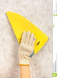 Hand With Spatula Smoothing Wallpaper On The Wall Stock Photo