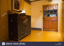 small wooden antique armoire and old door in the hallway inside an old 1722 french regime residential home