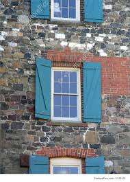 architectural details three antique open wooden shutters stone walls