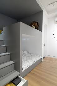 along one side of the bedroom is a grey alcove that s home to built in bunk beds with stairs leading to the top bed within the stairs are storage