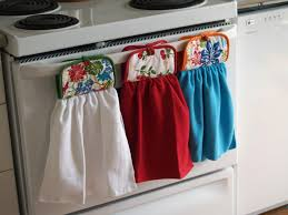 three colorful kitchen towels holder hanging on white cooktop combined with decorative kitchen towels