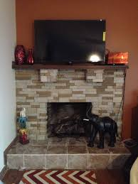 airstone surround the fireplace and matched with brown wall and wooden floor plus tv for