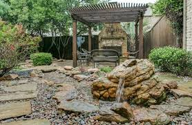 Backyard rock garden with small water feature and pergola