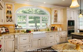 French Country Kitchen with Yellow Walls and Antiqued Cabinets