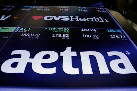 logos of cvs and aetna are displayed on a monitor above the floor of the new