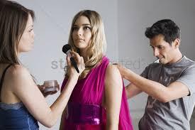 designer and makeup artist preparing model for photo shoot stock photo