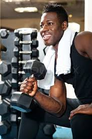 gym instructor young gym instructor toning his biceps stock photo colourbox