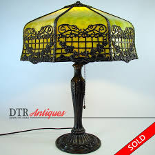 electric table lamp with green slag glass shade and intricate filigree work