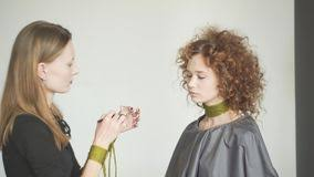 close up view to the professional makeup artist is applying red lip gloss to a