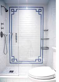 fantastic shower features white subway tile surround accented with blue greek key accent tiles as well as corner shower cads over mosaic shower floor