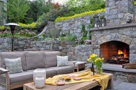 outdoor fireplace design come with grey sofa with wood frame and plywood table and concrete flooring