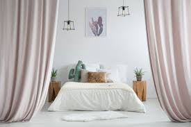 pastel curtains in rustic bedroom with white rug and cacti on wooden stools next to king