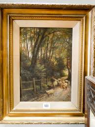 lot 888 an oil painting of sheep on a woodland path in a gilt frame