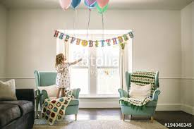 girl decorating balloons in living room for birthday party stock